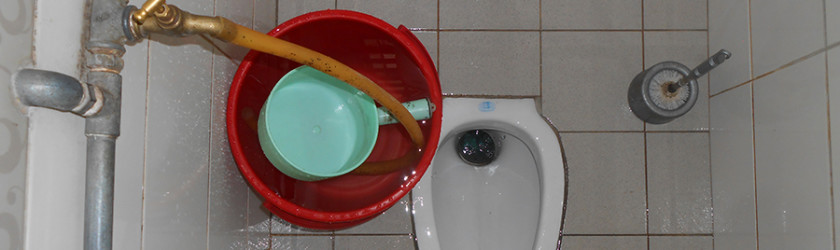 Squat toilet with bucket and scoop to wash your bum